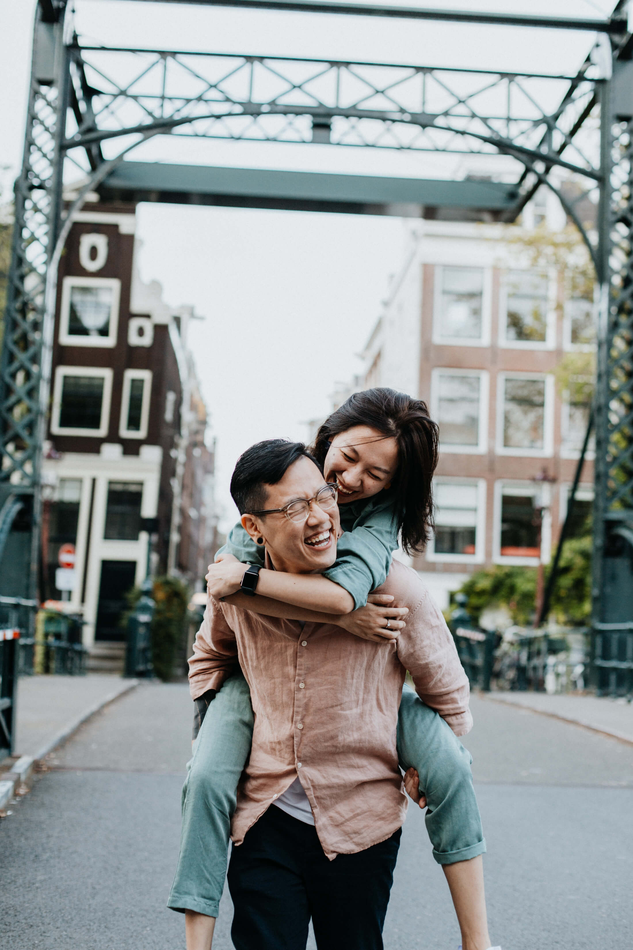 A man is kneeling on one knee and proposing to a woman on a bridge in Amsterdam. Both are wearing casual outfits. The woman is wearing a stylish jumper.