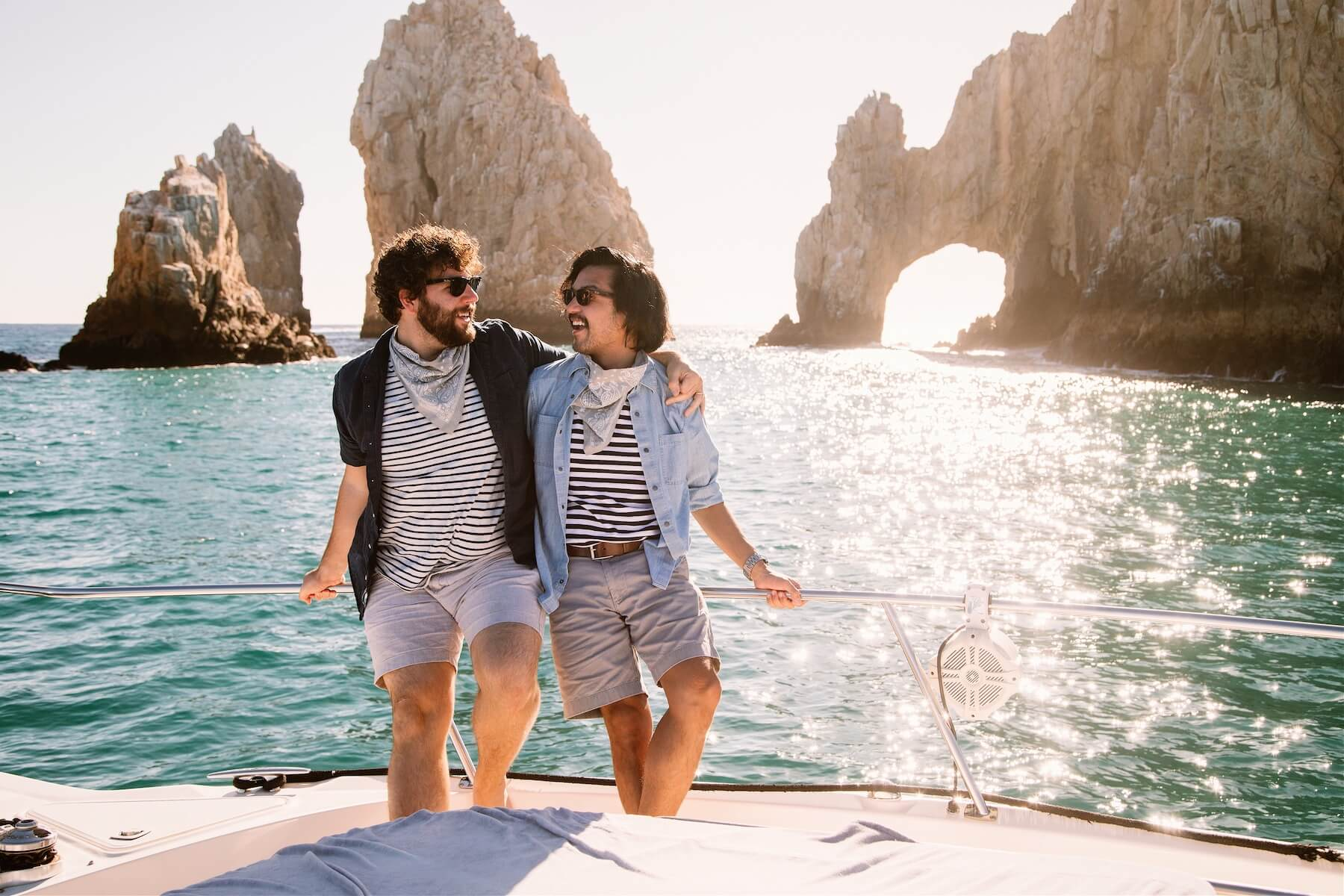 LGBT gay couple on a boat in front of the Arch of Cabo San Lucas in Mexico on a photo shoot with Flytographer.