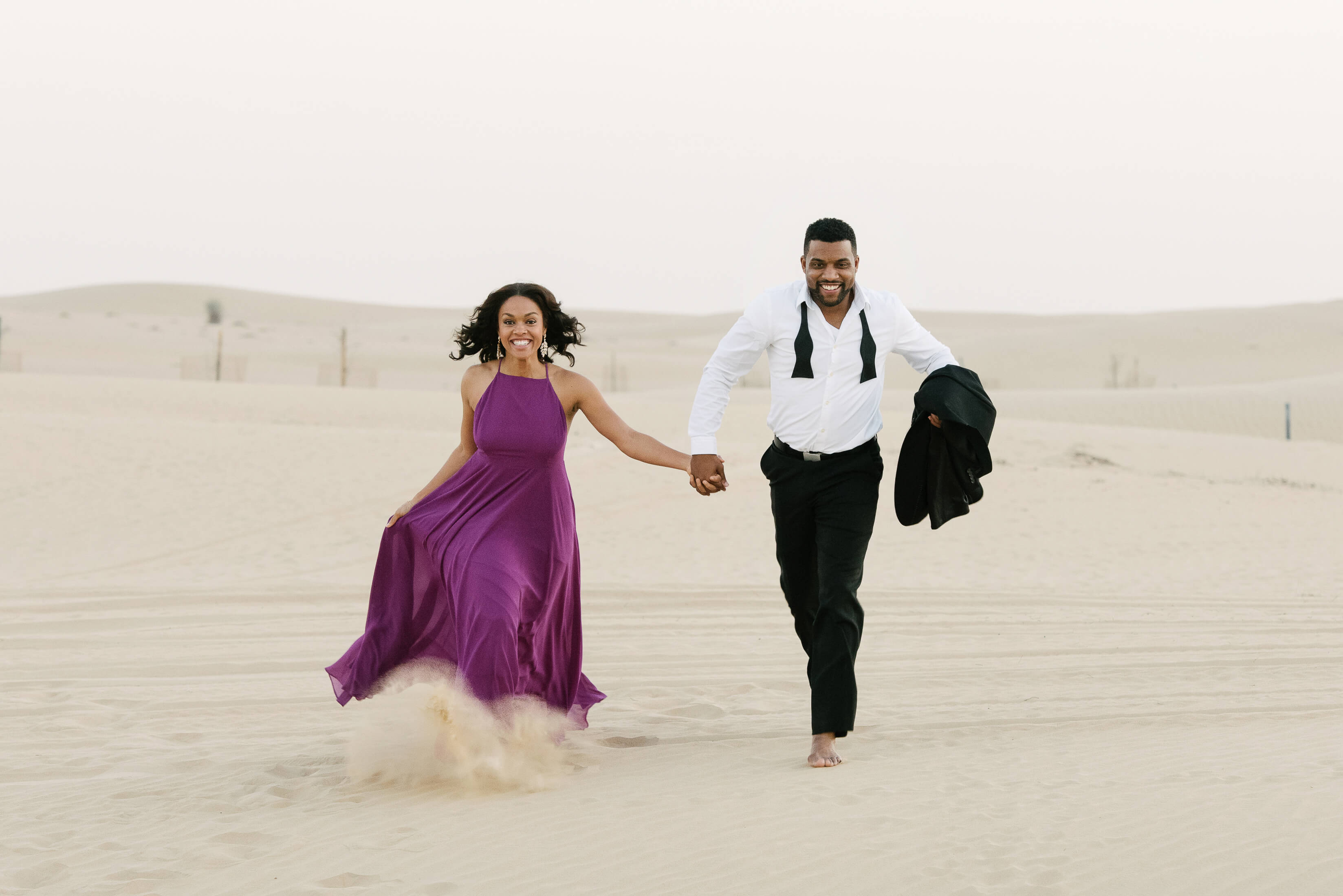 Couple holding hands and running in the desert in Dubai
