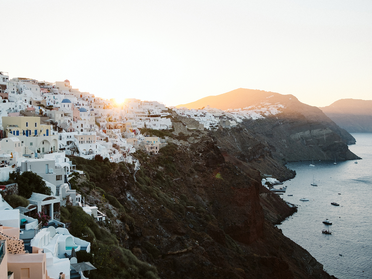 View from Oia Village in Santorini overlooking the Mediterranean Sea and white Santorini buildings.