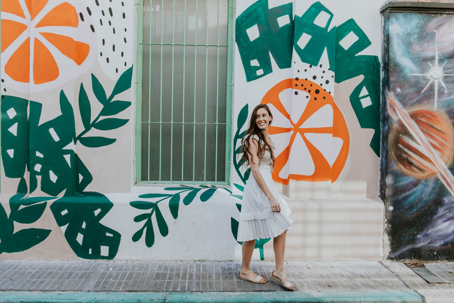 Woman walking in front of a colourful mural in Bueno Aires, Argentina