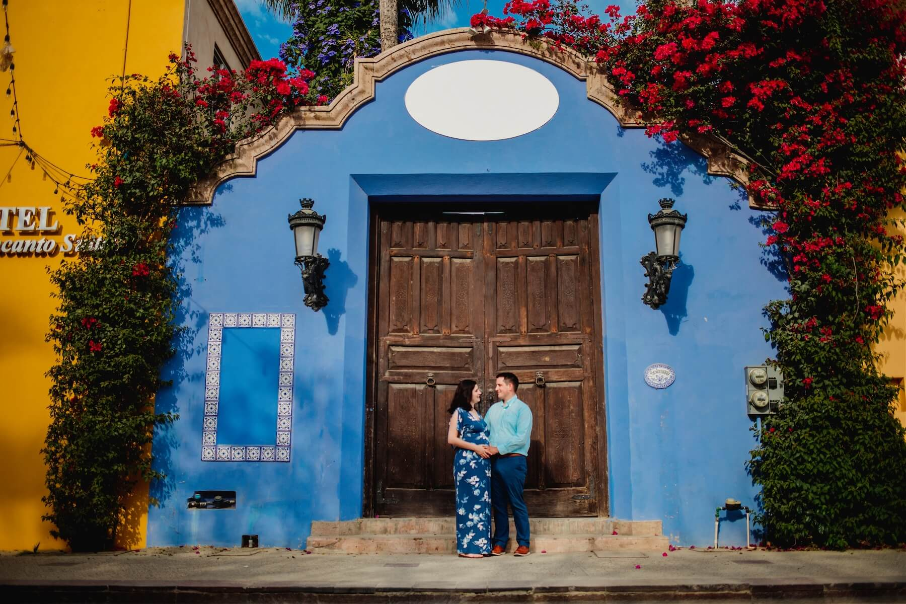 Couple standing against a colourful doorway in the Arts District of Cabo San Lucas on a maternity photoshoot with Flytographer