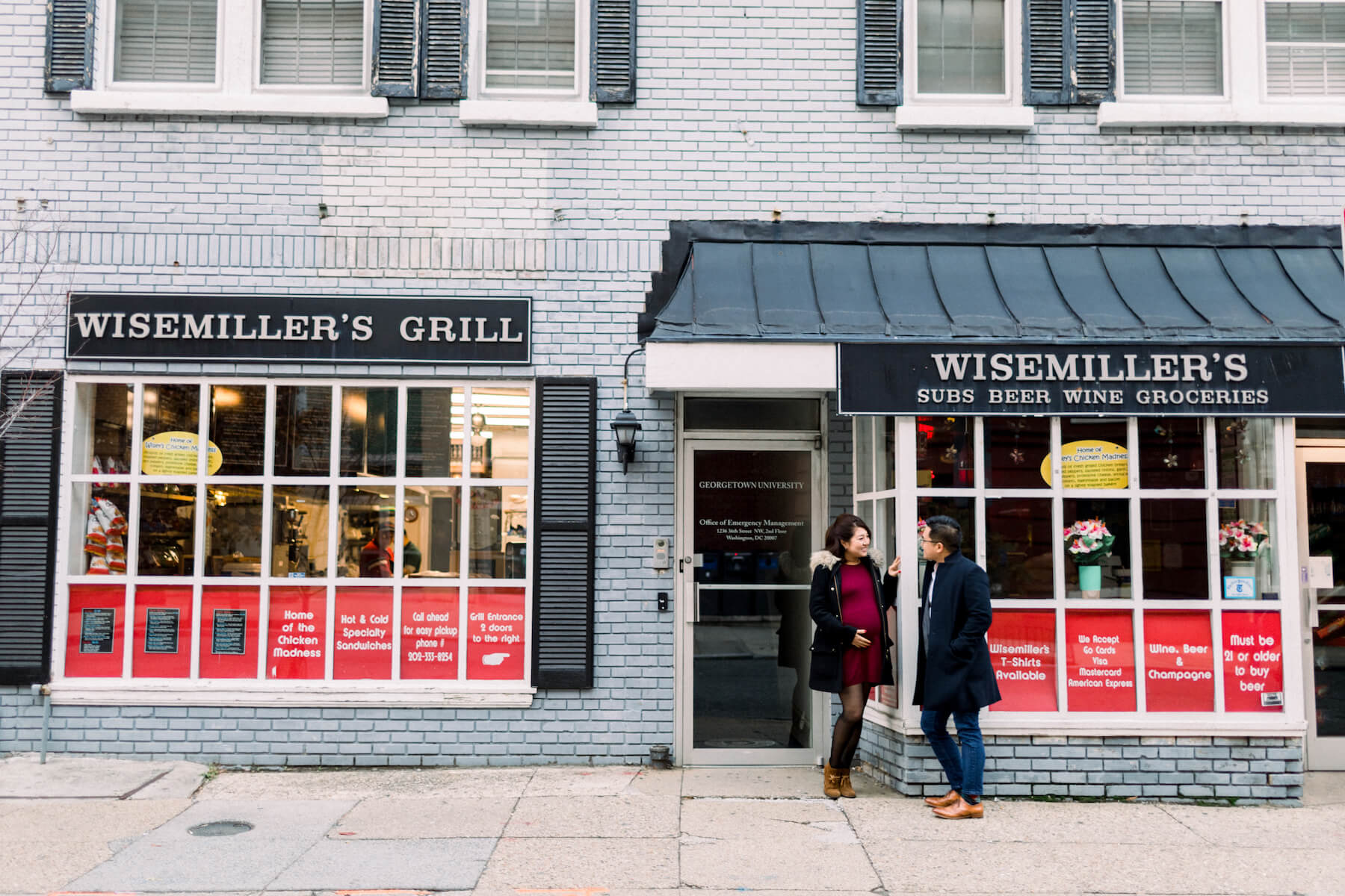 Couple pose in front of the Wisemiller's Grill in Washington DC on a couple photoshoot with Flytographer.