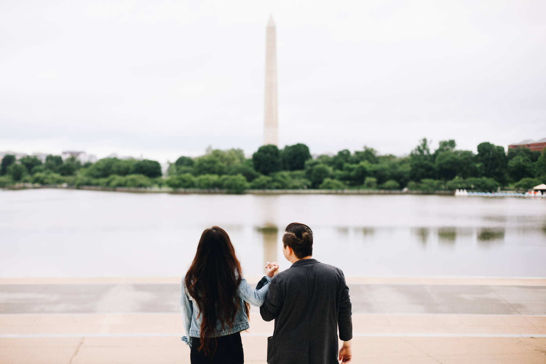 Couple on the steps of the Lincoln Memorial with the Washington Monument in the background in Washington DC on a couple photoshoot with Flytographer.