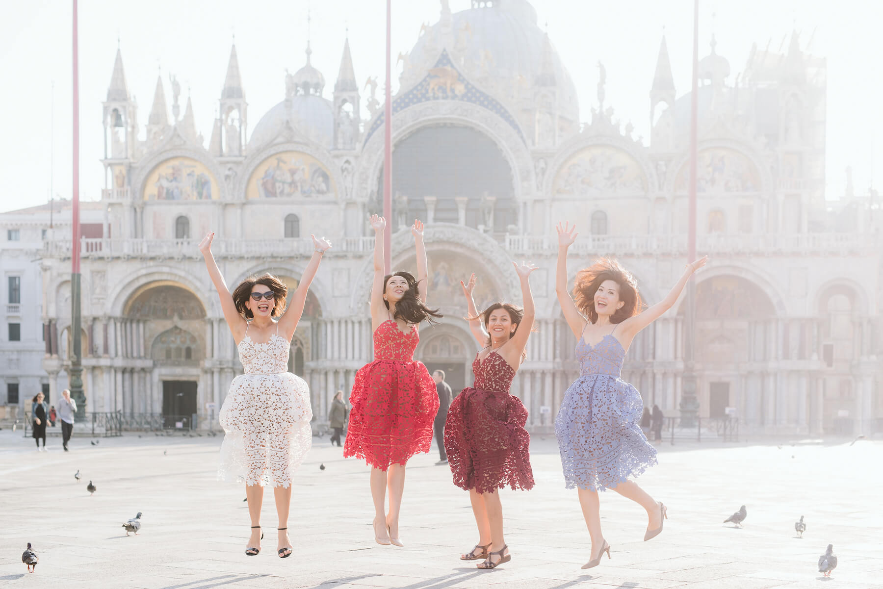 four ladies eating ice cream in Venice, Italy in pastel coloured dresses on a Flytographer friend photoshoot.