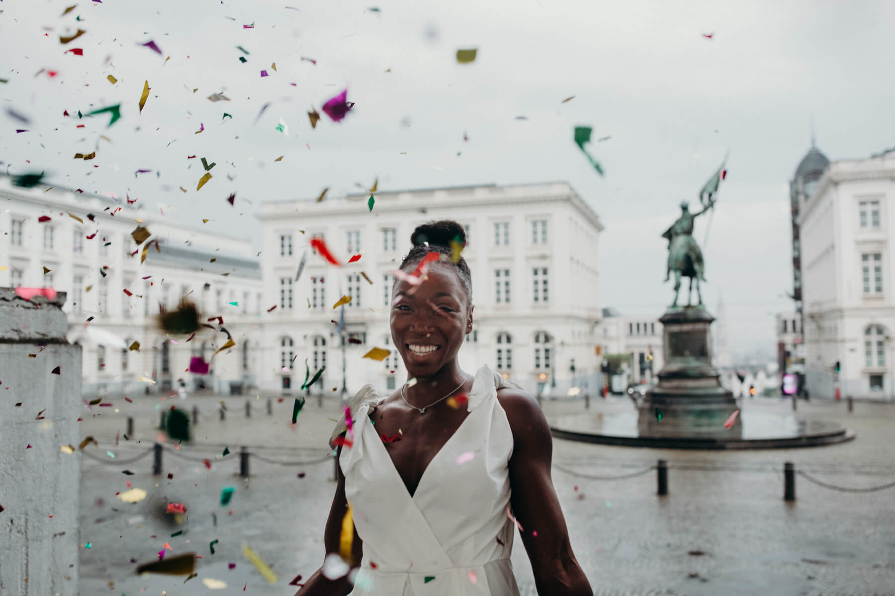 A woman celebrating her birthday with confetti and gold balloons wearing a white dress on a photoshoot with Flytographer.