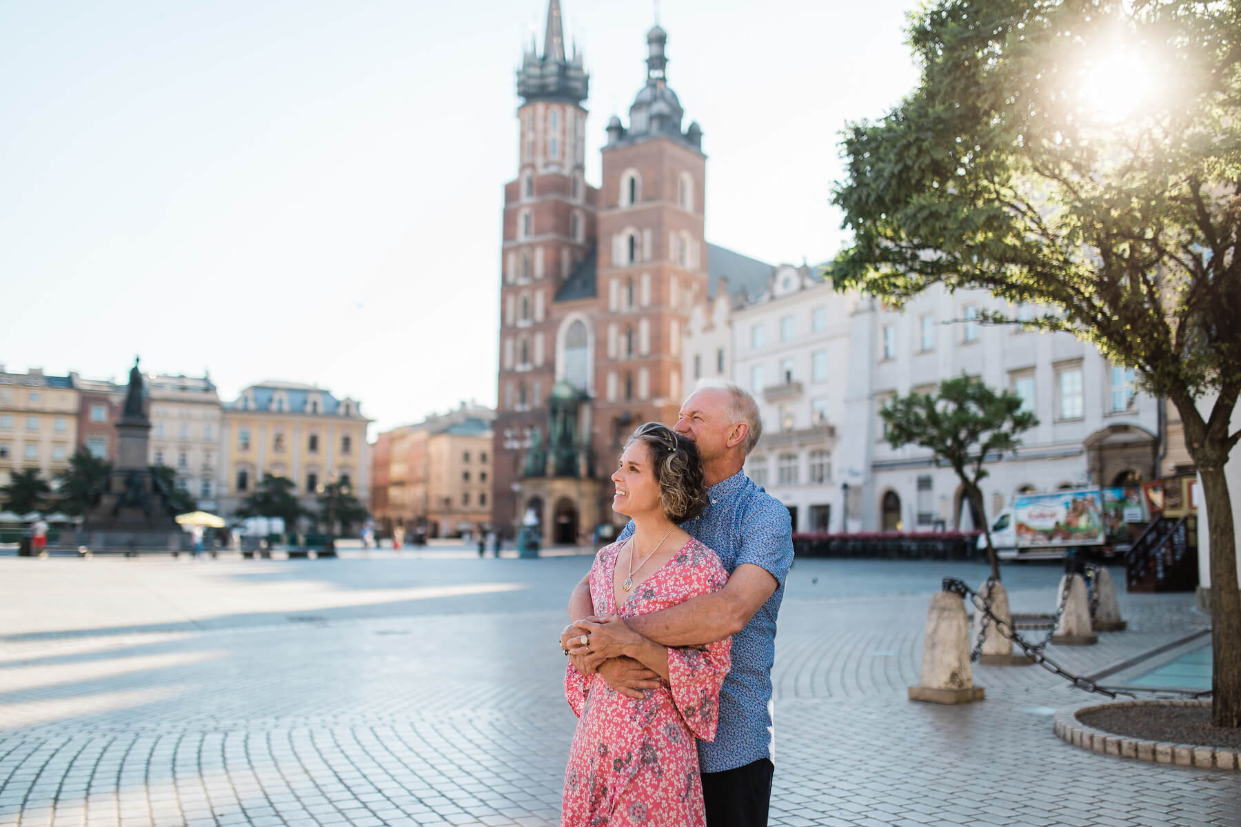 A couple hugging in the Main Square in Krakow, Poland on a couple photoshoot with Flytographer.