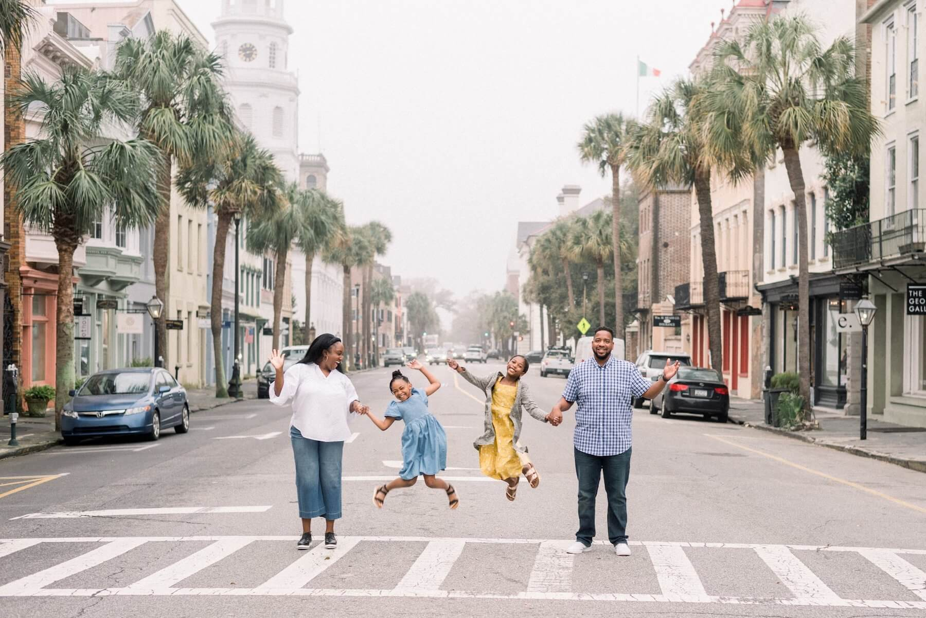 A family of four jumping in the streets of downtown Charleston on a family photoshoot with Flytographer.