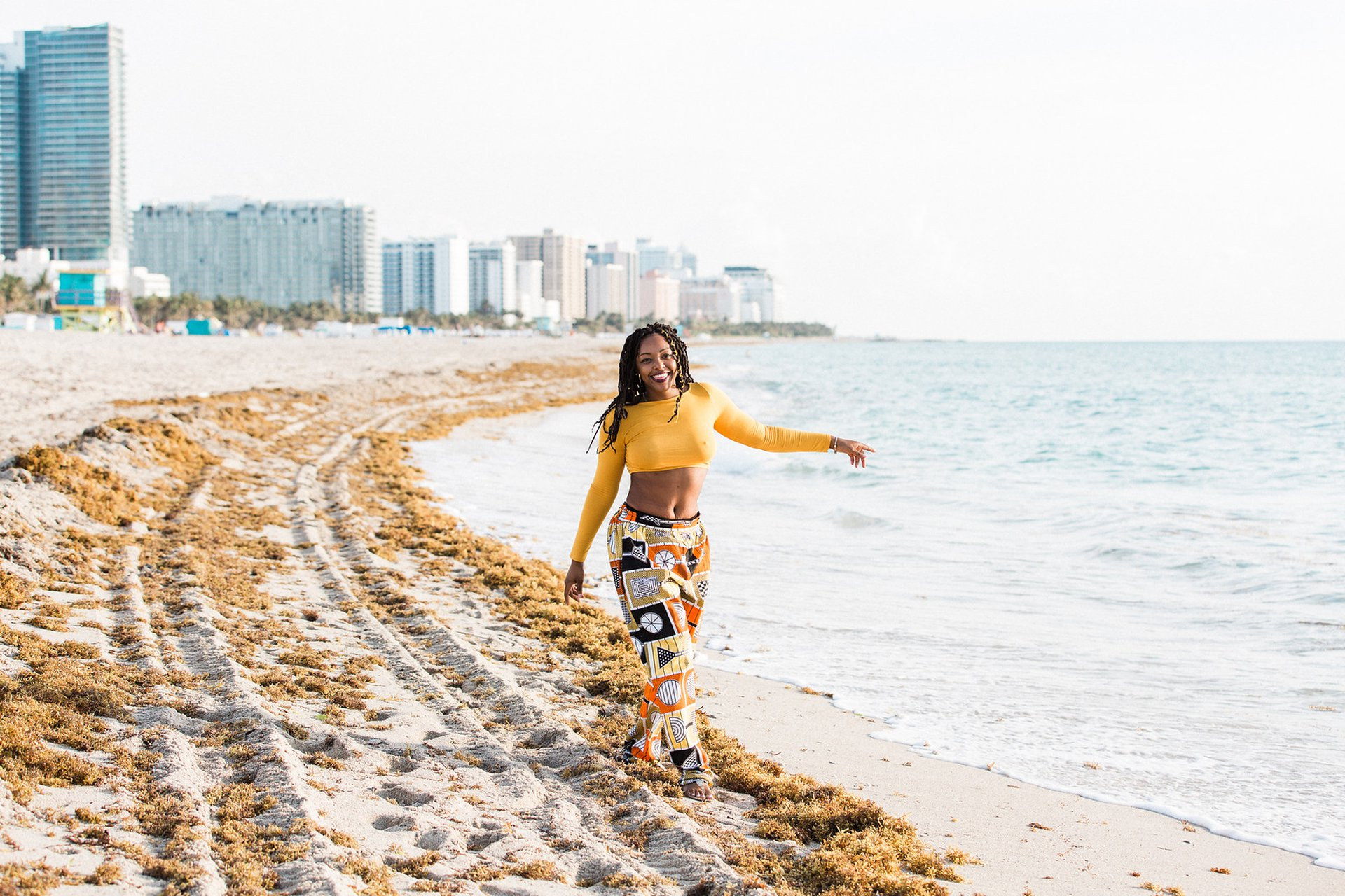 woman walking on South Beach in Miami wearing an orange top and pants captured by Flytographer.