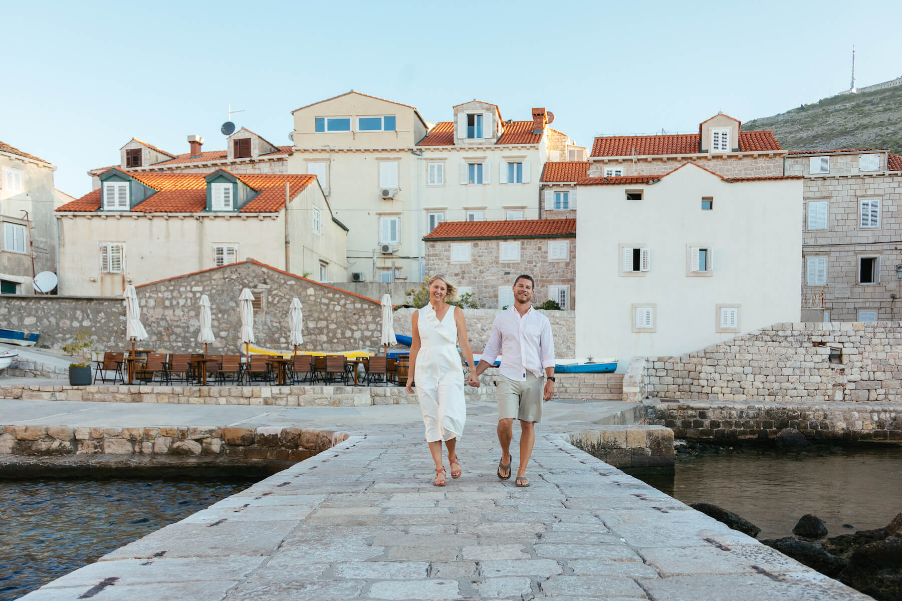 a woman in a white jumpsuit and their partner are holding hands and taking photos on a photoshoot with Flytographer in Dubrovnik, Croatia.
