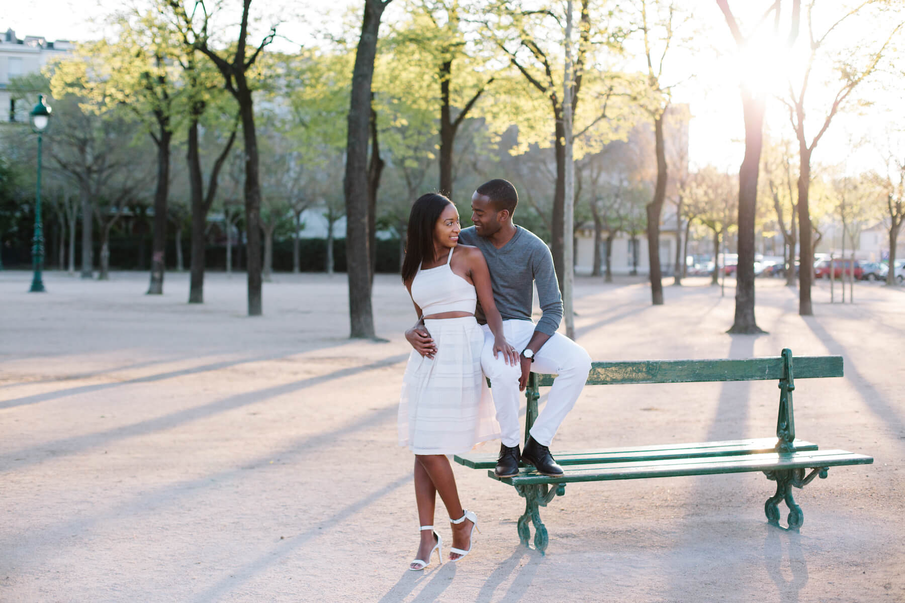 A couple sitting on a park bench in Paris, France on a couple photoshoot with Flytographer.