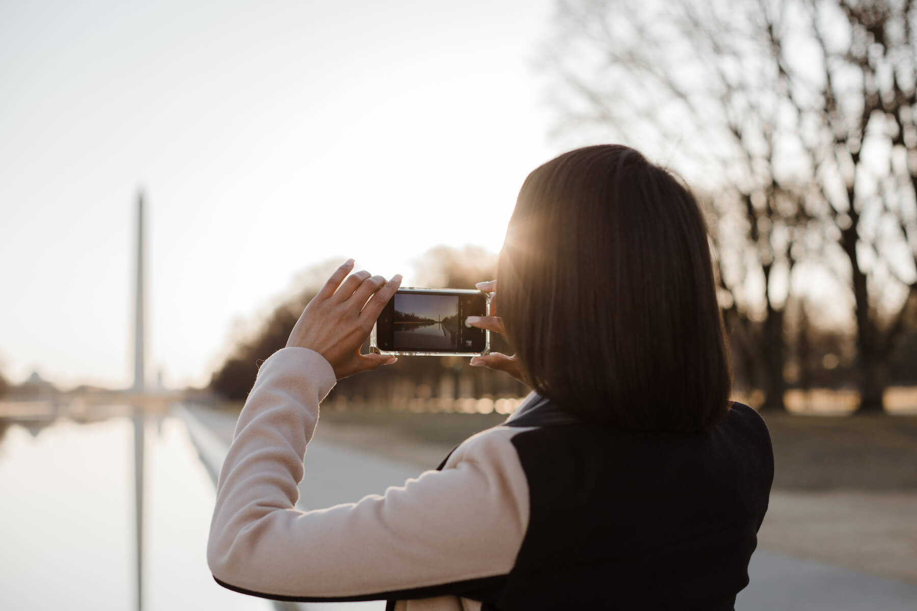 A woman on her iPhone taking photos and the best iPhone photography tips