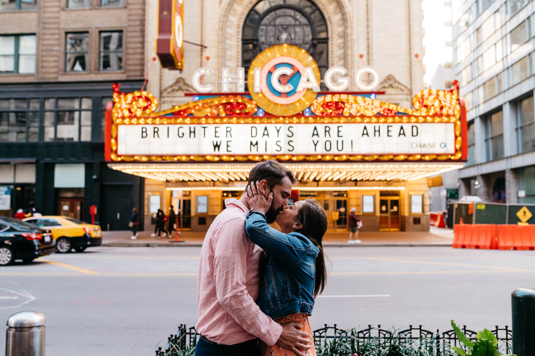 A couple kissing in front of the Chicago Theatre in Chicago on a couple photoshoot with Flytographer.
