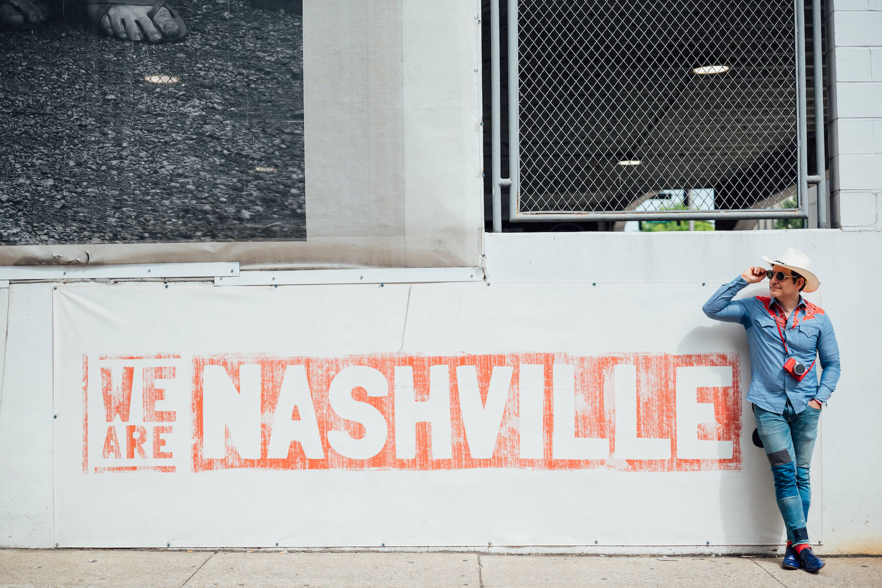 """A man standing up against the """"We are Nashville"""" mural in Nashville on a Modern headshot photoshoot with Flytographer."""